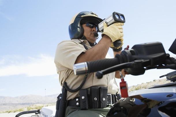 Traffic police officer looking through a radar gun