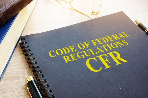 A book of Federal Regulations, pens, and glasses on a table