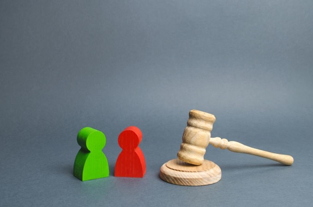 A conceptual image about court proceedings, depicting two opponent figures beside a judge's gavel.