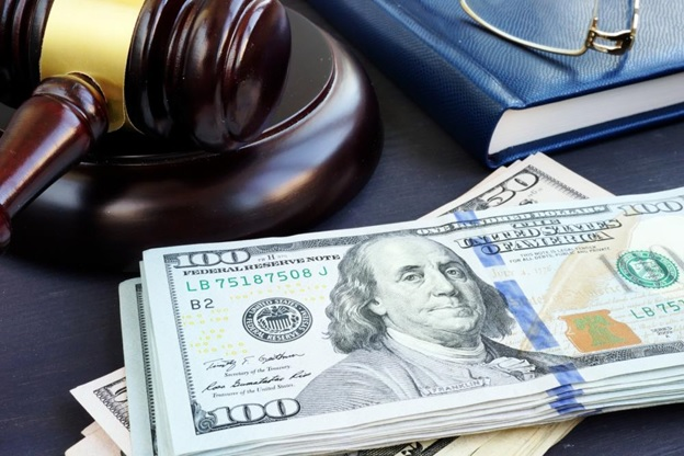 Cash and a judge's gavel lying on a surface, a conceptual image about bail