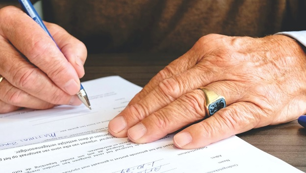 A man wearing a blue ring and signing papers of release
