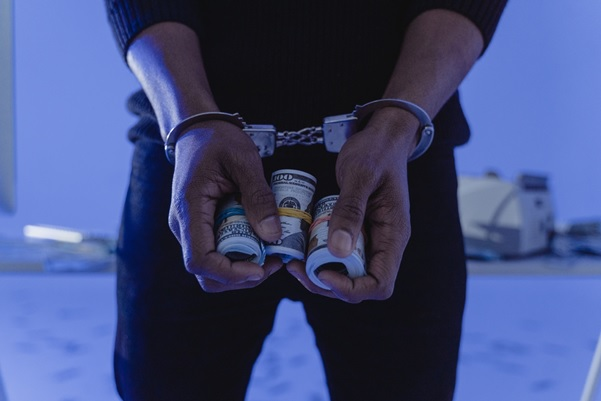 A person handcuffed and holding rolls of hundred-dollar bills in their hand