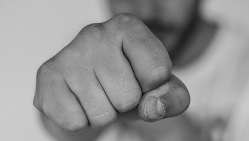 An individual raising his fist to protect himself from an attack.