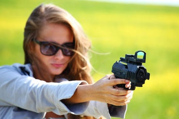 Woman in Indiana pointing down a scoped pistol
