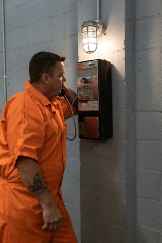 An inmate making a phone call in prison