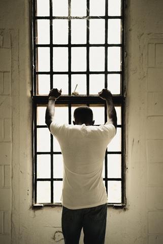Man leaning on jail windows.