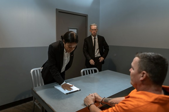 Two police detectives interrogating a handcuffed inmate
