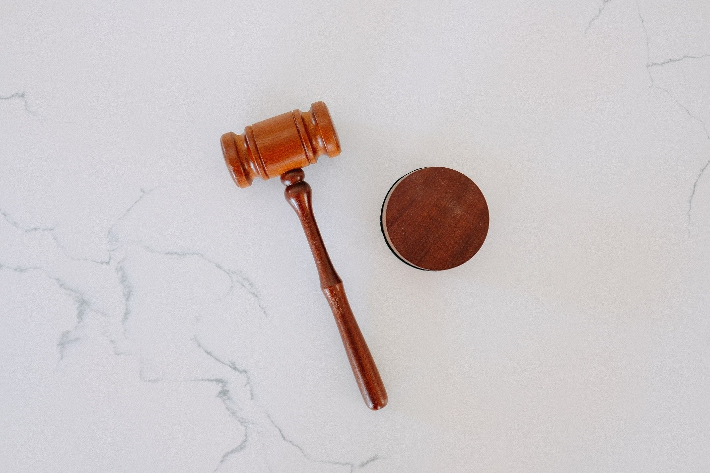 A wooden gavel on a white marble table