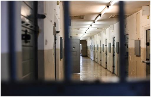 Locked jail cell door in a corridor