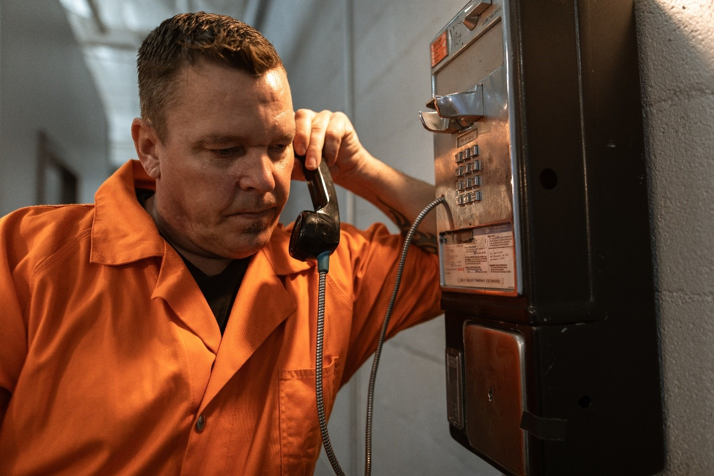 Man calling his friend from a payphone in prison