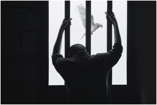 Man in jail holding onto the steel bars