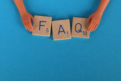 FAQ spelled out on wooden tiles against a blue background.