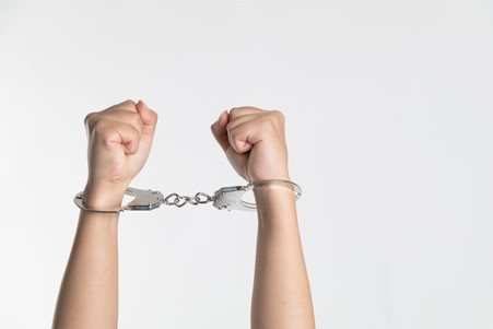 Person holding up handcuffed hands.