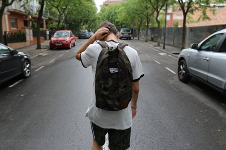 Teenager walking on the road with head bowed down.