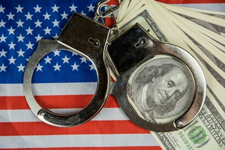 US flag, handcuffs, and dollar bills.